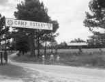 Boys standing beside the sign at the entrance of Camp Rotary in Elmore County, Alabama.