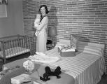 Mrs. Robert A. Moorhead holding her baby, Robert, in a room at Doby's Hotel Court at 3453 Mobile...