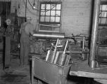 Employee operating machinery at the Continental Gin Company in Prattville, Alabama.