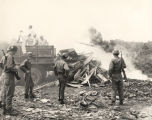 National Guardsmen observing burning pile of rubble.
