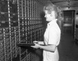 Woman pulling a safe deposit box in the vault of the First National Bank of Montgomery in downtown...