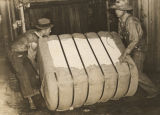 Two workers lifting a bale of cotton in Houston County, Alabama.