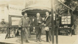 Three men standing in front of display offering information about Muscle Shoals, Alabama.