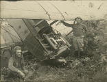 Two pilots standing in front of a crashed biplane at Camp McClellan in Anniston, Alabama.