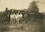 Young men standing in front of a wrecked train in Alabama.