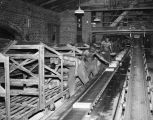 Employees placing bricks on a conveyor belt at Jenkins Brick Company, at the intersection of 8th...