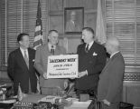 "Mayor William A. Gayle holding a ""Salesman's Week"" sign in his office in Montgomery,..."