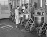 Man operating equipment at Hollywood Nut Products Company at 8 Lafayette Street in Montgomery,...