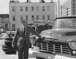 Man standing beside a truck of the Fowler-Dozier Tire Service at the corner of Bibb and Coosa...