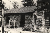 Two women gathering wood outside a native stone vacation cottage in Cheaha State Park in Alabama.