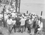 Men gathered at the shore under the first aid station at a regatta sponsored by the Montgomery...