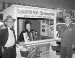 Members of the Salvation Army board of counselors at the Christmas donation booth in front of the...