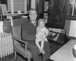 Captain Arthur C. Ross holding a little girl in his office at the West End Salvation Army on...