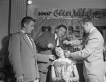 Three men styling a woman's hair during a convention of beauticians in Montgomery, Alabama.