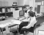 Man working at a computer in an office area at the Western Electric material management center on...