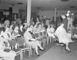 Hairstyling demonstration at a convention hosted by the Johnson's Beauty and Barber Supply...