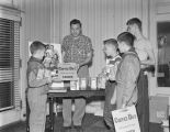 Boy Scouts preparing to deliver American Cancer Society Coffee Day coin cans and posters to people...