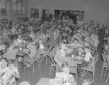 Children eating in a lunchroom, possibly as part of a free lunch program sponsored by the United...