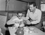 Mike Miaoulis serving a football on a plate to a man at the Seven Seas Restaurant in Montgomery,...