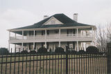 Two-story white house with a wraparound porch in Ohatchee, Alabama.