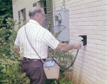 Man using a water meter manufactured by the Neptune Meter Company in Tallassee, Alabama.