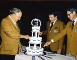 Members of the Kiwanis Club cutting a cake to celebrate the twenty-fifth anniversary of the South...