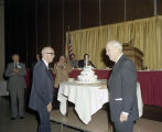 Judge Richard Rives and another man standing in front of a birthday cake during a luncheon for the...