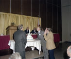 Men blowing out the candle on a birthday cake during a luncheon for the Alabama State Bar at the...