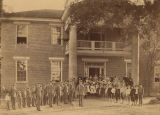 Boys and girls gathered outside a large brick building.
