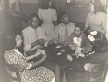 African American soldiers and young women playing cards at the USO in Mobile, Alabama.