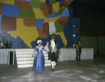 Man and woman in colonial costumes walking in front of the stage at the El Domino Ball at Garrett...