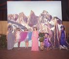 Women in costumes in front of a painted scene during the Les Mysterieuses Mardi Gras ball at...
