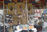 Jimmie and Jimmie Pruett, members of the Kiwanis Club, standing on the carousel at the 1974 South...