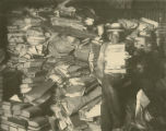 Copy photograph of Pat Pinkston moving unprocessed archival material in the basement of the...