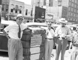 Sam Engelhardt and other men standing with a bale of cotton on the sidewalk on Commerce Street in...