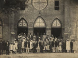 Members of an African American congregation standing in front of a  church building.