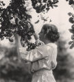 Helen Keller picking fruit from a tree.