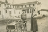 Man and woman stand in front of the Red Cross building at Camp Sheridan in Montgomery, Alabama.