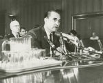 George Wallace speaking into microphones while seated at a table, possibly during a testimony...