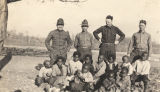Four soldiers standing with a group of African American children.
