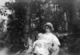Man holding a baby, possibly William Gulley Simpson, while seated in front of a tree in the woods,...