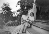 Woman reading to a child, possibly William Gulley Simpson, on the porch steps of the Simpson home...