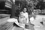 Woman bathing a baby, possibly Hugh Lewis Simpson, on the front porch of a house, probably in...