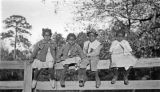 Four African American children sitting on a fence in Wilcox County, Alabama.