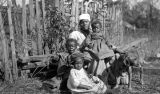 African American woman with three children and a dog in front of a wooden fence in rural Wilcox...