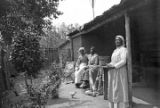 Three African American women with quilts outside a cabin in rural Wilcox County, Alabama.