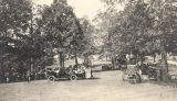Automobiles and carriages parked under trees at a gathering in Pintlala, Alabama.