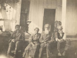 Four African Americans sitting on a porch in Fort Mitchell, Alabama.