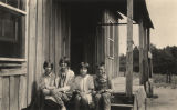 Four children sitting on the porch of a cabin in Sylacauga, Alabama.