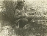 Hunter crouched in front of a tree with a turkey caller in his hand and a gun in his lap.